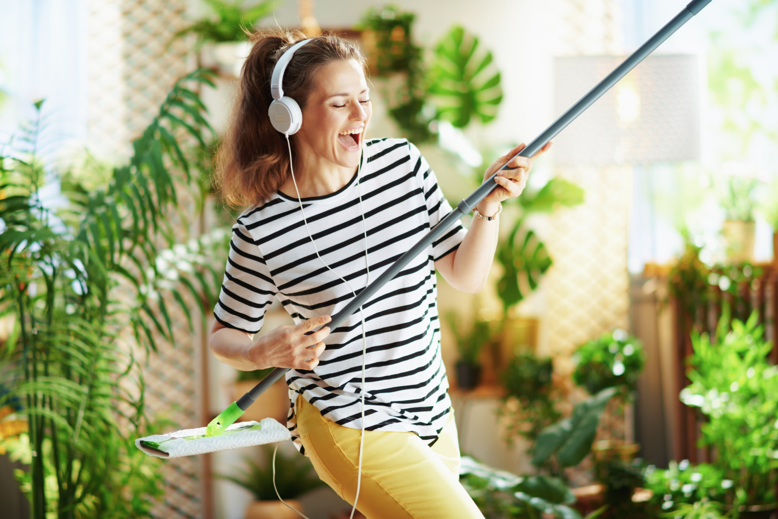 smiling woman in striped shirt in sunny day doing housekeeping