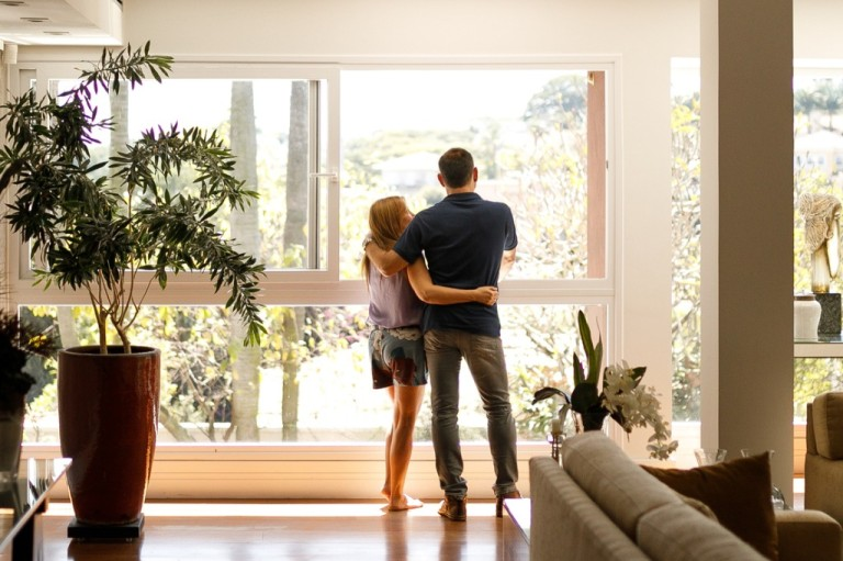 couple-admiring-the-view-from-the-living-room-of-their-house-picture-id1146103884