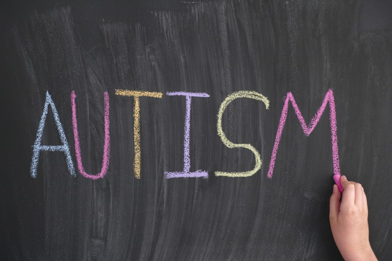 Child writing the word Autism on a blackboard